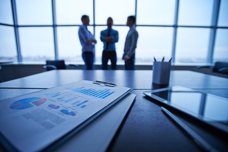 Business documents, pen and touchpad on the table on background of group of businessmen interacting by the window in office