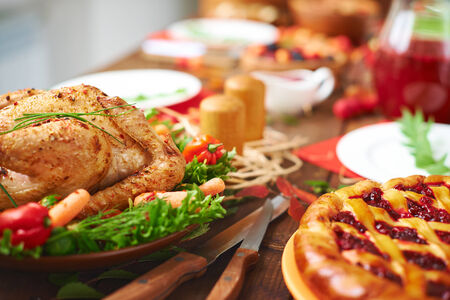 traditional christmas dinner: Roasted meat with garnish and cowberry pie on festive table Stock Photo