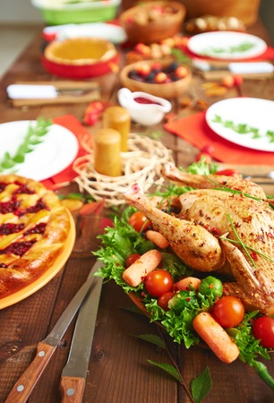 festive food: Roasted turkey with spices and vegetables and other festive food on served table Stock Photo
