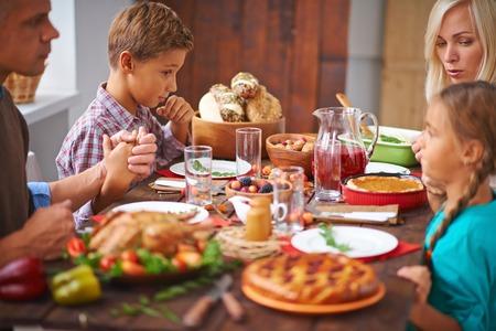 familia orando: Retrato de familia moderna orando antes de la cena festiva