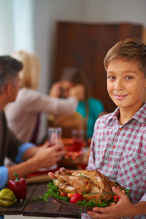 Portrait of adorable boy with roasted turkey looking at camera with smile photo