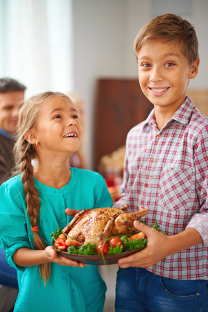 Portrait of cute siblings with roasted turkey garnished with vegetables on plate photo