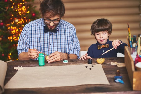 man painting: Portrait of father and son preparing Christmas picture at home