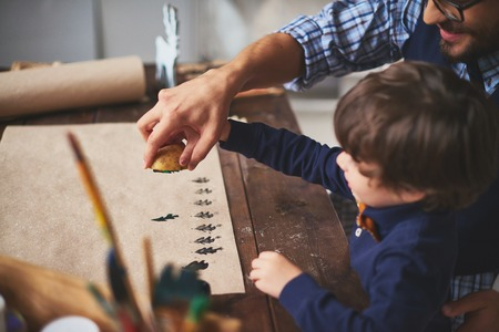 xmas crafts: Young man teaching his son how to print on paper with help of potato and gouache