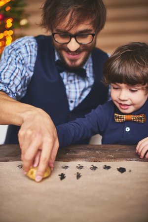 art and craft equipment: Young man teaching his son how to print firtrees on paper Stock Photo