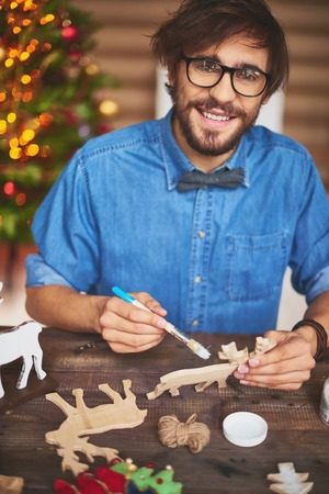 Happy young man preparing wooden shape of deers for Christmas photo