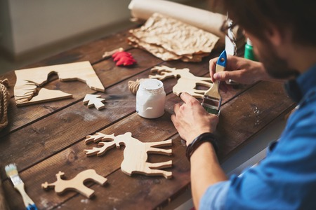craftsmen: Young craftsman painting wooden deers for xmas Stock Photo