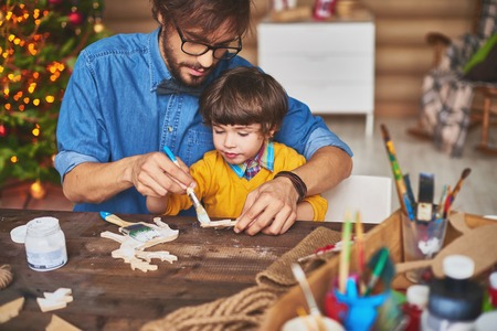 christmastide: Young father showing his son how to paint wooden deers
