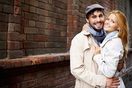 smiling: Portrait of smiling couple in stylish trench-coats looking at camera outside