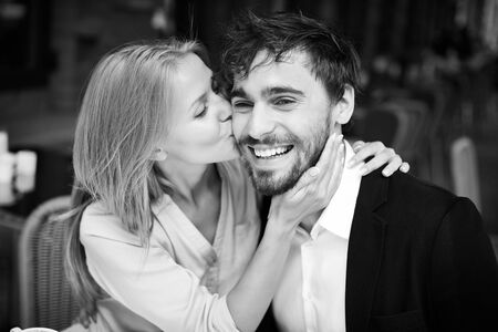 young couple smiling: Lovely girl embracing and kissing her boyfriend