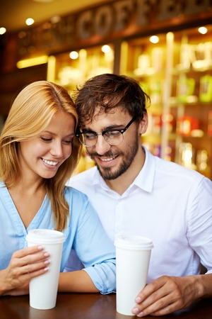 restful: Portrait of restful couple with drinks in plastic containers sitting in cafe Stock Photo