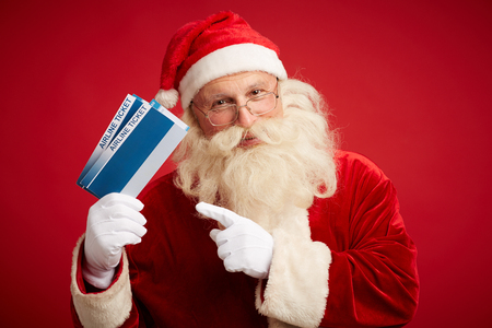 generous: Kind Santa Claus with two airline tickets looking at camera over red background
