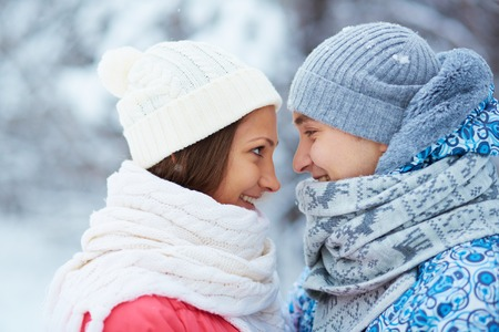 winterwear: Profiles of dates in winterwear smiling at one another outdoors