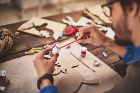 Close-up of craftsman painting xmas symbols with white gouache photo