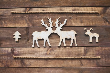 White wooden deers kissing between two ropes photo