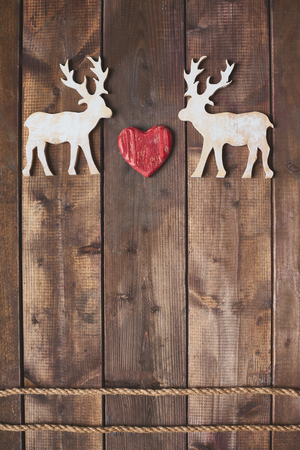 White wooden deers with red heart between them over two ropes photo