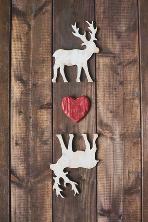 White wooden deers with red heart between them photo