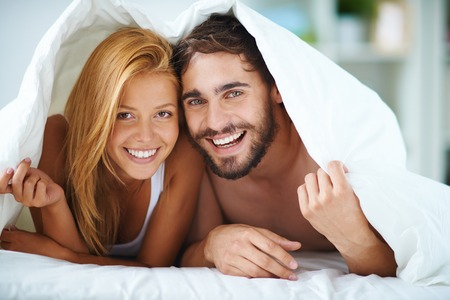 romance bed: Affectionate man and woman under blanket looking at camera with smiles Stock Photo