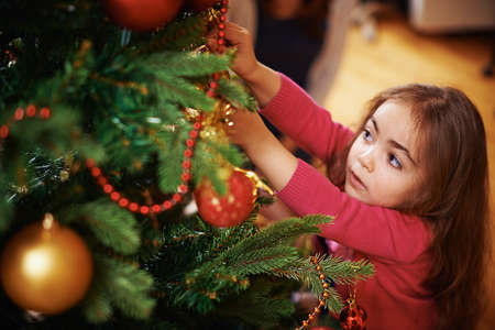 decorating christmas tree: Cute little girl decorating Christmas tree Stock Photo