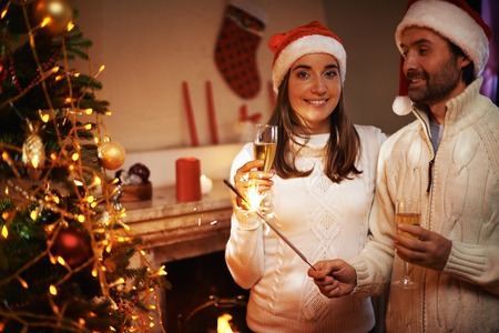 pullovers: Happy couple in Santa caps and white knitted pullovers holding flutes with champagne Stock Photo