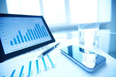 recursos financieros: Los documentos impresos y electrónicos, lápiz, teléfono celular y vaso de agua en el lugar de trabajo Foto de archivo