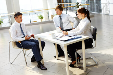 Young businesswoman and businessman looking at their boss explanations at meeting photo