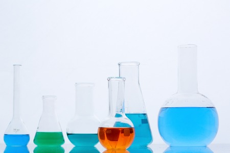 liquid material: Row of flasks with multi-color liquids in isolation