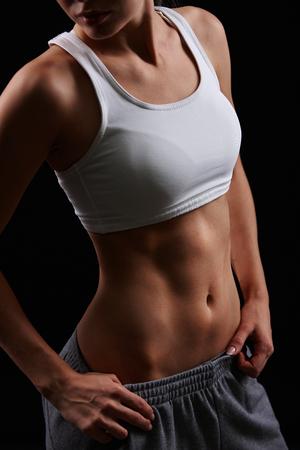 Fit female in sportswear posing in isolation