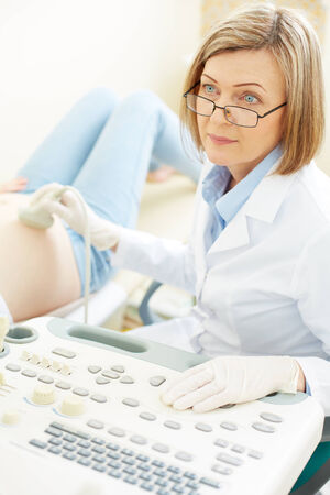 obstetrician: Serious obstetrician making an ultrasound examination to pregnant woman in hospital
