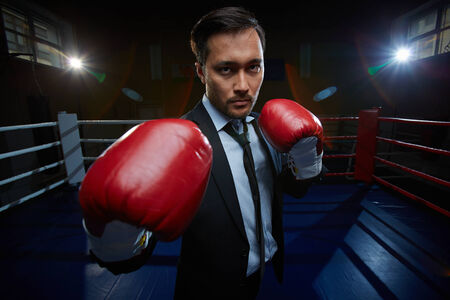 Serious businessman in suit and boxing gloves looking at camera