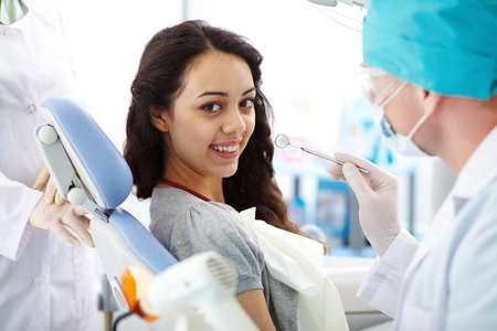 Cute brunette with toothy smile looking at camera before dental check-up Stok Fotoğraf
