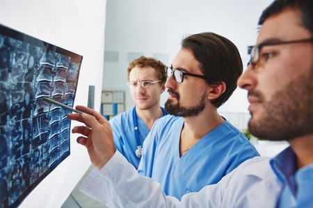 healthcare workers: Young male doctor pointing at x-ray and discussing it with colleagues