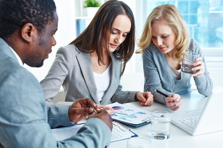 Business team analyzing financial document at meeting photo