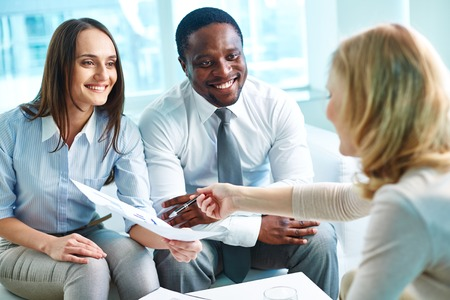 Young businesswoman explaining her partners data on paper at meeting photo