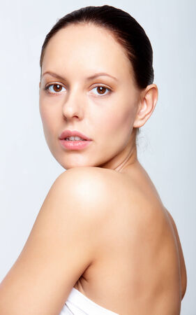 Gorgeous woman with natural makeup posing for camera in isolation photo