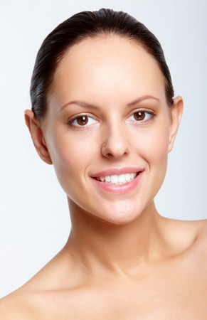 Charming female looking at camera with toothy smile photo