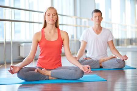 nirvana: Calm girl and guy doing yougs exercise for relaxation Stock Photo