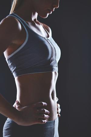 activewear: Body of slim female in activewear keeping her hands on waist