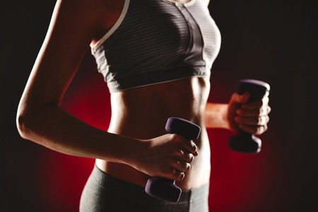 activewear: Female torso in activewear during exercise with dumbbells