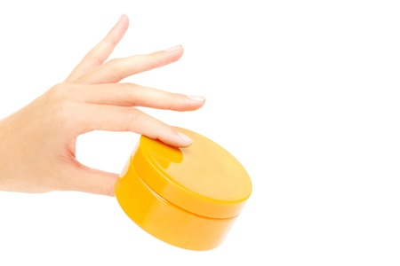handcare: Female hand holding container with cream or scrub in isolation