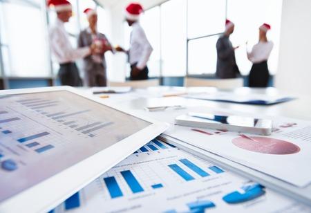 서류, 터치 패드 및 핸드폰 직장에서 산타 모자 상호 작용하는 사무실 근로자의 배경에 확대해서