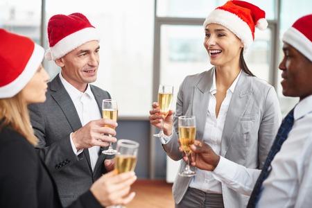 Šťastné obchodních partnerů v Santa čepice držení flétny s šampaňským na firemním večírku Reklamní fotografie