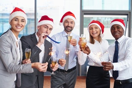 Group of successful colleagues in Santa caps having Christmas party in office
