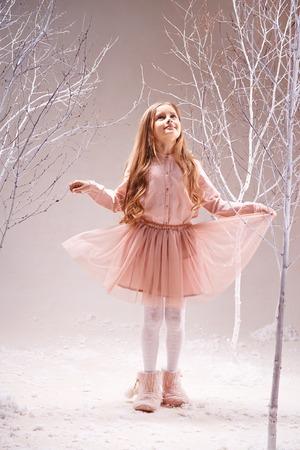 Niña linda en vestido rosa caminando en el bosque mágico entre árboles desnudos Foto de archivo