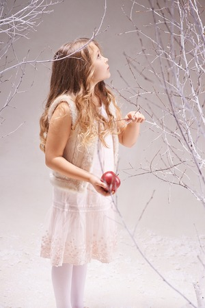 Cute little girl with red apple standing among bare trees photo