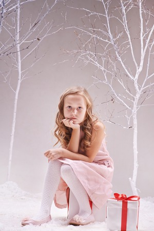 Adorable little girl sitting on giftbox and looking at camera in wonderful forest photo
