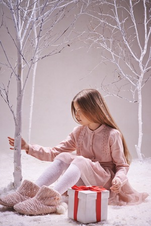 Cute girl with giftbox near by sitting in winter forest and touching bare tree trunk photo