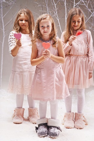 Three charming girls holding candy hearts, one of them looking at camera photo
