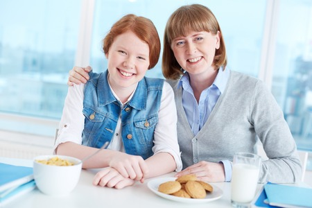 Cute teenage girl and her mother looking at camera with smiles during breakfast Stock Photo
