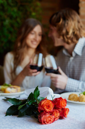 Bunch of fresh roses on served table and young dates toasting on background photo